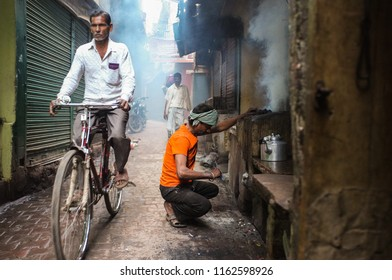 VARANASI, INDIA - 20 FEBRUARY 2015: Street vendor makes fire for milky tea in coal oven while cyclist passes.