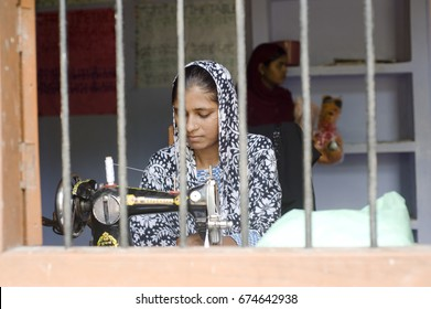 Varanasi / India 20 September 2011  Indian Women Working on Sewing Machine  in front of window at Varanasi Uttar Pradesh India