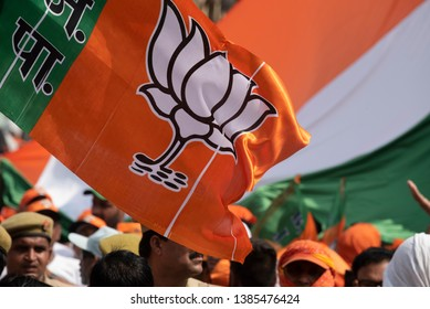 Varanasi / India 25 April 2019 BJP party workers and supporters waved the Lotus print flags during PM Narendra Modi road show in Varanasi northern Indian state of Uttar Pradesh