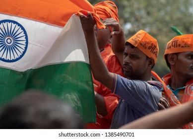 Varanasi / India 25 April 2019 Bharatiya Janata Party (BJP) supporters wave Indian national flag during a roadshow by PM Narendra Modi in Varanasi Uttar Pradesh