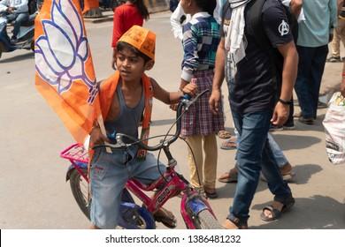 Varanasi / India 25 April 2019 BJP young supporter waive party flags during Prime Minister Narendra Modi  roadshow in Varanasi Uttar Pradesh