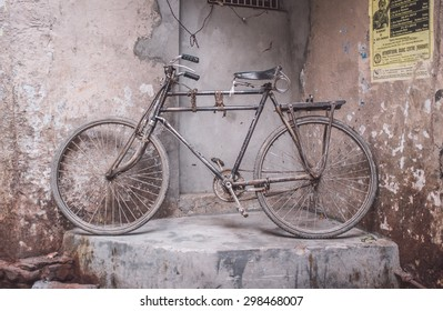 VARANASI, INDIA - 25 FEBRUARY 2015: Traditional Indian bicycle parked in corner of street. Post-processed with grain, texture and colour effect.
