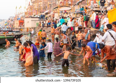 Varanasi, India, 27 Mar 2019 - Showing the colorful traditional clothing and Hindu religious ritual of bathing in the Ganges River from the ancient ghats of Varanasi