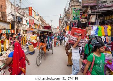 VARANASI, INDIA - 27 Oct 2016: Bicycle rickshaw driver rides through the street market at Dasaswamedh Ghat on October 27, 2016 in Varanasi, India