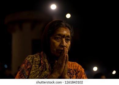 Varanasi / India 9 December 2018 Elderly traditional indian woman with two hands together in a prayer posture in Ganga Aarti ceremony at Dashashwamedh Ghat in Varanasi Uttar Pradesh India