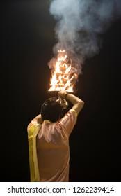 Varanasi / India 9 December 2018 Indian Priest Performs Religious Ganga Aarti with hand held multiple layer oil lamps in front of Ganga river at Dashashwamedh Ghat in Varanasi Uttar Pradesh India