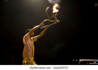 Varanasi / India 9 December 2018 Indian Priest Performs Religious Ganga Aarti with hand held oil lamps in front of Ganga river at Dashashwamedh Ghat in Varanasi Uttar Pradesh India