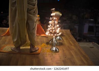 Varanasi / India 9 December 2018 Indian Priest stands near hand held multiple layer oil lamps during Religious Ganga Aarti at Dashashwamedh Ghat in Varanasi Uttar Pradesh India