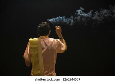 Varanasi / India 9 December 2018 A hindu brahmin priest performing ganga aarti with agarbatti or incense stick at Dashashwamedh Ghat in Varanasi Uttar Pradesh