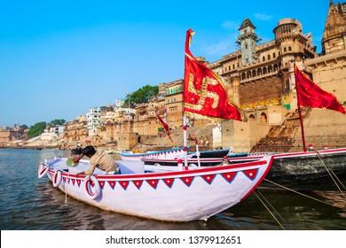 VARANASI, INDIA - APRIL 12, 2012: Colorful boat with swastika aryan symbol and Ganges river bank in Varanasi city in India