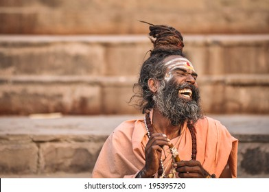 Varanasi, India - April 19, 2010: Happy Guru Laughing in joy at Ganga river. The most holy river of India and Hindu culture.