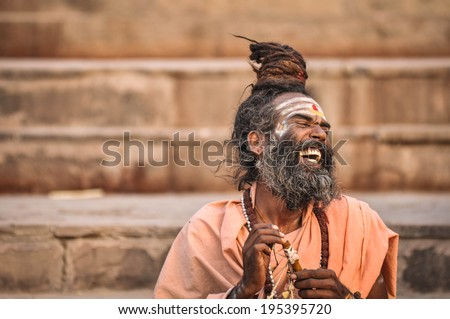 Varanasi, India - April 19, 2010: Happy Guru Laughing in joy at Ganga river. The most holy river of India and Hindu culture.