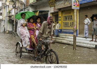 VARANASI, INDIA - AUGUST 11: Cycle rickshaw and passengers try to make headway through flood waters after monsoon storm in a busy street on August 11, 2011 in Varanasi, Uttar Pradesh, India.