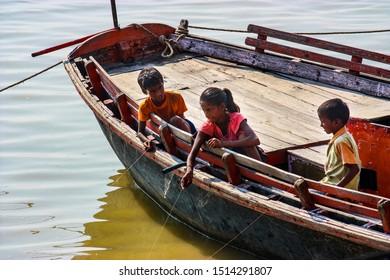 Varanasi, India - August 20, 2009: three children fishing with a line from a boat in Varanasi, Uttar Pradesh, India