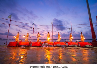 Varanasi, India, August 2017: Seven Young priests perform the holy Ganga aarti ceremony rituals with holy fire at dawn at the Ganges river bank at Varanasi, India. Sunset light with beautiful colors