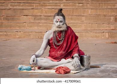 VARANASI, INDIA - DECEMBER 1, 2012 : Unidentified Hindu sadhu holy man, sits on the ghat near the Ganges river in Varanasi, India. Tourism has drawn many alleged fake sadhus to Varanasi