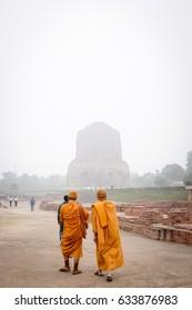 VARANASI, INDIA - DECEMBER 2, 2016: Buddhist monks and tourists come to visit and pray in the misty morning at Dhamekh Stupa, the Buddhist historic landmark of Sarnath, Varanasi, India.