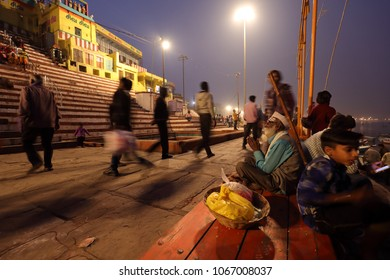 VARANASI - INDIA - DECEMBER 2, 2017: Unidentified Hindu pilgrims in the evening on the ghats on December 2, 2017 in Varanasi, India. Varanasi is the holiest of the seven sacred cities in India