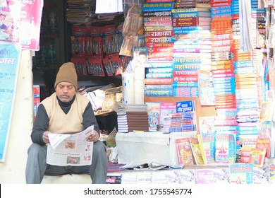 Varanasi, India - December 28, 2018 : Indian small shop owner selling religious & mythological books in Varanasi, India. Local small businesses depend of tourism for their livelihood