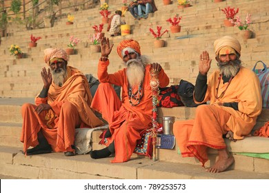 VARANASI, INDIA - DECEMBER 3, 2017: Three Hindu ascetics wave while sitting on the steps leading down to the sacred Ganges River in Varanasi, India.
