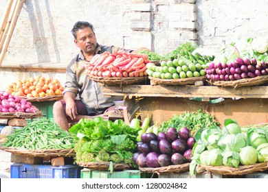 Varanasi, India - December 30 2018 : Indian vegetable seller at food market in Varanasi, India. Small vegetable & fruit vendors are sold in road side shops through Indian cities & towns