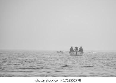 VARANASI, INDIA - FEB 14 2019: People travelling in a boat in a misty morning