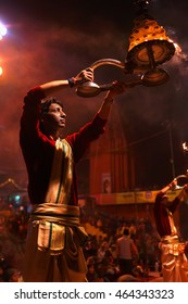 Varanasi, India - February 05, 2014: Hindu priest, young indian man, brahman, during night religious hindu Ganga Aarti ceremony for Mother Ganges, river and goddess, at Dashashwamedh Ghat, Varanasi