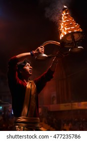 Varanasi, India - February 05, 2014: Hindu priest, young indian man, brahman, during night religious hindu Ganga Aarti ceremony (fire puja ritual) for Ganges, at Dashashwamedh Ghat, Varanasi