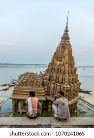 VARANASI, INDIA - February 16, 2017: Two Indian devotees meditate in front of the ancient submerged Shiva Temple at Scindia Ghaat in Varanasi, India