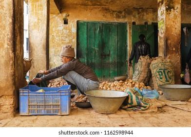VARANASI, INDIA - FEBRUARY 20, 2015: Street vendor prepares his shop for selling his potato produce.