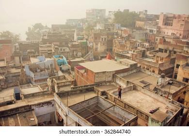 VARANASI, INDIA - JAN 3: Fog over historical indian city with brick buildings with grunge walls on January 3, 2013. Varanasi urban agglomeration had a population of 1,435,113