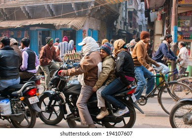 VARANASI, INDIA - JAN 4: Unidentified children and them father on the motorcycle ride on the crowed city with of cycles on January 4, 2013. Varanasi urban agglomeration had a population of 1,435,113