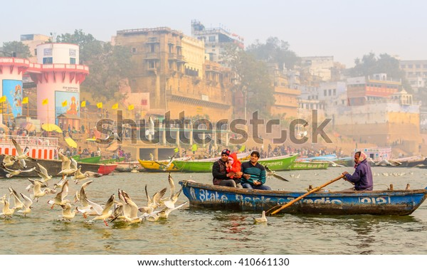 Varanasi, India - January 17, 2016: Indian child and parents playing with seagulls at the popular boat tour on the sacred Ganges river in Varanasi, Uttar Pradesh, India