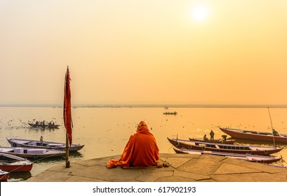 VARANASI, INDIA- January 18, 2017:Indian sadhu in traditional saffron attire practicing yoga and meditation in morning at the bank of sacred Ganges river in Varanasi, Uttar Pradesh, India.