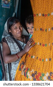 Varanasi, India - January 19, 2019: Mother and her kid in front of their house in rural areas of Varanasi.