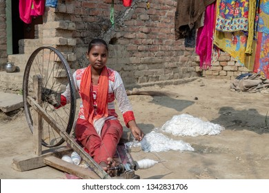 Varanasi, India - January 19, 2019: Traditionally dressed young Indian woman use traditional wheel ( yarn spinner ) and spin yarn in front of her house in a village near Varanasi,India.