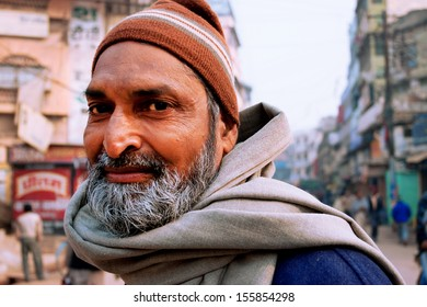 VARANASI, INDIA - JANUARY 2: Portrait of an bearded Indian passer on the crowded indian street at evening on January 2, 2013. Varanasi urban agglomeration had a population of 1,435,113