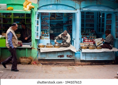 VARANASI, INDIA - JANUARY 2: Traditional street life with a sellers of small spices shops & passers-by people at morning on January 2, 2013. Varanasi urban agglomeration had a population of 1,435,113