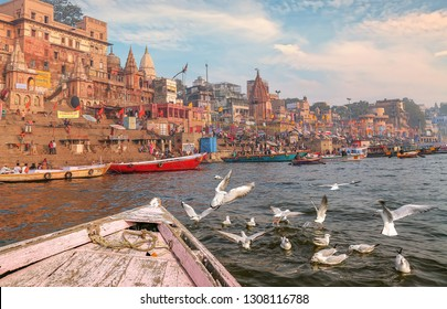 Varanasi, India, January 21,2019: Varanasi Ganges river ghat with ancient architecture buildings as viewed from a boat with migratory birds on river Ganga.