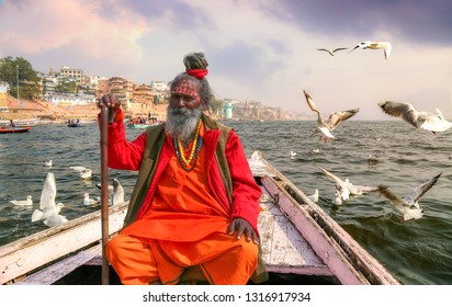 Varanasi, India, January 21,2019: Holy Sadhu baba sitting on a wooden overlooking ancient Varanasi city architecture with Ganges river ghat at sunset. Migratory birds are seen flocking around the boat