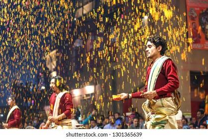 Varanasi, India, January 21,2019: Young priests showring flower petals as part of a ritual ceremony during Ganga worship (Aarti) at Dashashwamedh Ganges river ghat at Varanasi India
