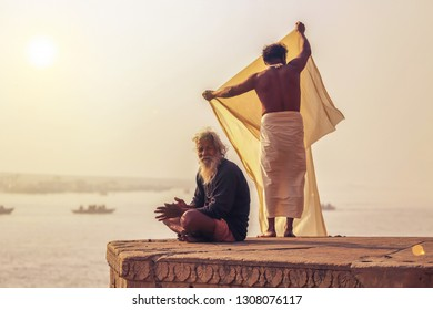 Varanasi, India, January 22, 2019: Aged man prepares for meditation while a pilgrim dries his clothes at Varanasi Ganges river ghat on foggy winter morning