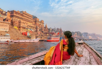 Varanasi, India, January 22, 2019: Ancient Varanasi city architecture with Ganges river bank. Indian female tourist enjoy boat ride on the river Ganges