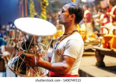 Varanasi, India, January 23,2019: Hindu priest playing the music instrument Damaru which signifies Lord Shiva at Varanasi Ganga aarti ritual ceremony