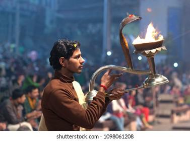 VARANASI, INDIA - JANUARY 3, 2016: Young Indian Brahmin conducts religious Ganga Maha Aarti ceremony (fire puja) at Dashashwamedh Ghat