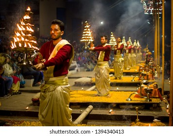 Varanasi, India : January 8, 2019 - Holy priests in their traditional prayer dress performing the ceremonial Ganga aarti (prayer) at Dashashwamedh Ghat in evening with candles in a winter evening