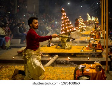 Varanasi, India : January 8, 2019 - Holy priests are performing the famous evening aarti ( prayer ) at Dashashwamedh ghat with candles in their half standing position
