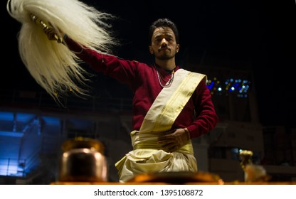 varanasi, India : January 8, 2019 - A priest offering puja with a chamar (yak tail hand fan) during the famous Ganga aarti (prayer) at Dashashwamedh Ghat