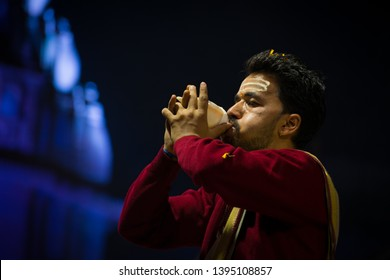 Varanasi, India : January 9, 2019 - A hindu priest blowing conch shell in traditional style as a part of the famous Ganga Aarti (prayer) at Dashashwamedh Ghat