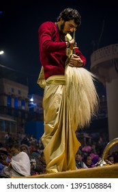 Varanasi, India : January 9, 2019 - A priest gives pranaam (salutation) with chamar (yak tail fan) at the end of Ganga aarti (prayer) at Dashashwamedh Ghat